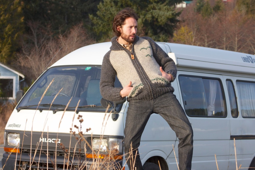 Fine looking man in a fine looking sweater in front of a fine looking van